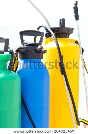 Three pressure sprayers for gardening arranged one next to other - stock photo
