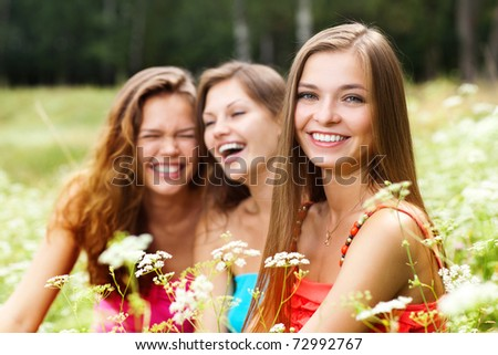 three pretty caucasian girls sitting down on green grass - stock photo