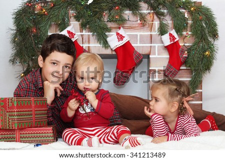 Three pretty children sitting near Christmas decorated fireplace, winter holiday family concept