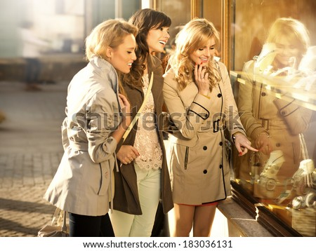 Three pretty girlfriends looking at the shop window - stock photo