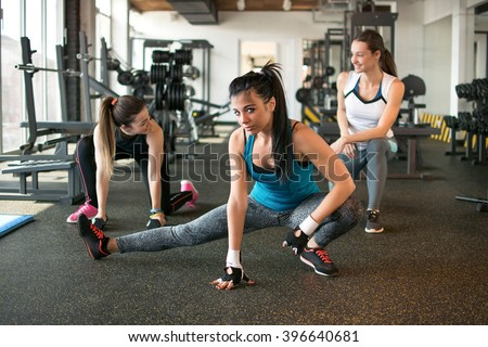Three pretty girls doing exercises in the gym.