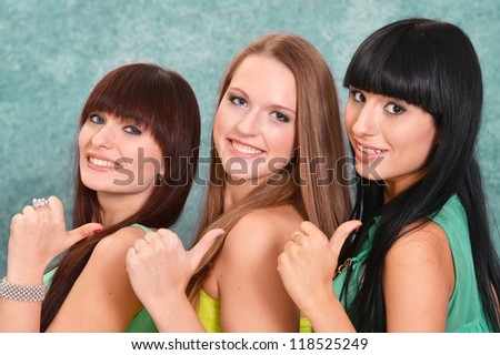 three pretty girls in green dresses on a green background - stock photo