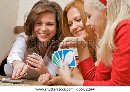 Three pretty girls lying on the floor, playing a game of cards UNO. - stock photo