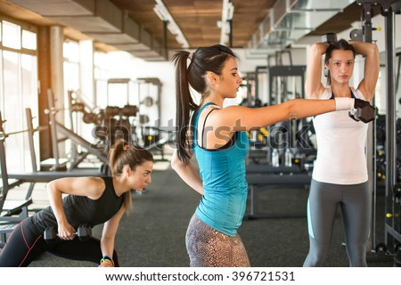 Three pretty girls workout in the gym.