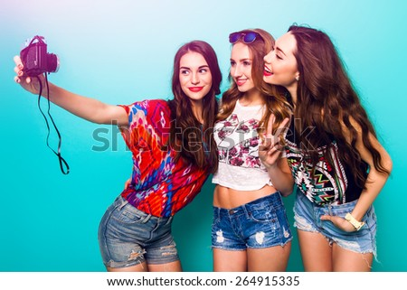 Three  pretty sexy  girls  taking self portrait . Wearing bright  summer stylish outfit and jeans shorts .  They smiling and  do hand sings against blue wall. - stock photo