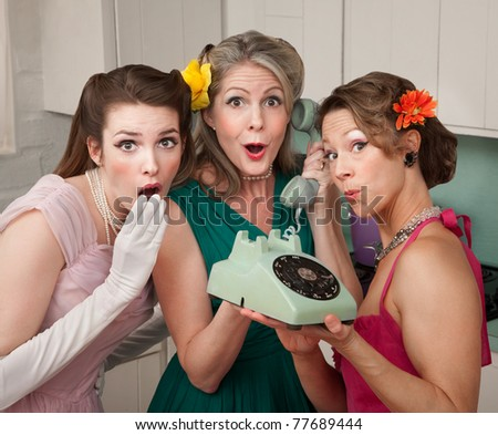 Three pretty women in kitchen with telephone - stock photo