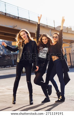 Three pretty young girls having fun outdoors . Lifestyle urban mood.  Evening city background. Best friends wearing  black casual outfit.  - stock photo