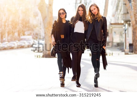 Three pretty  young girls having fun outdoors together . Lifestyle urban mood.  Center city background. Best friends wearing black casual outfit. - stock photo