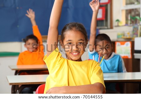 Three primary school children hands raised in class - stock photo
