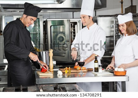Three professional chefs working in commercial kitchen - stock photo