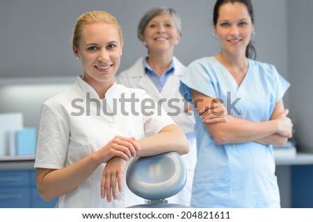 Three professional dentist woman team standing dental surgery  looking camera - stock photo