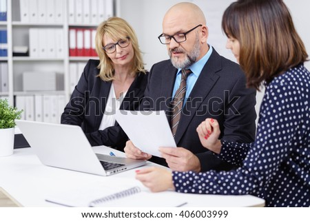 Three professional workers meeting and discussing something important while seated at white table with laptop computer - stock photo