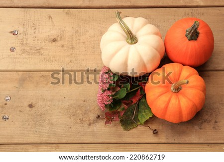 Three pumpkins on wood background with autumn leaves and flowers. Halloween or Thanksgiving decor. Halloween or Thanksgiving decor. - stock photo