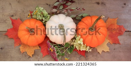 Three pumpkins on wood background with autumn leaves and flowers. Halloween or Thanksgiving decor. - stock photo
