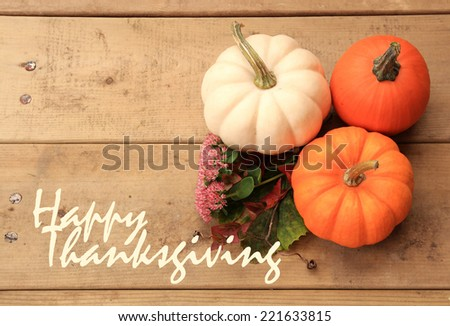 Three pumpkins on wood background with autumn leaves and flowers with the phrase �« Happy Thanksgiving �» on the left.