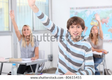 Three pupils in class with arms raised