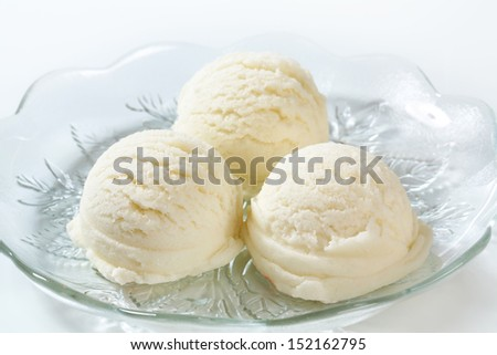 three pure white ice cream scoops on a glass plate