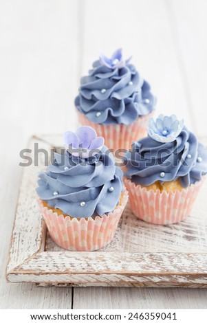 Three purple cupcakes with buttercream frosting swirl, silver pearls and edible flowers - stock photo