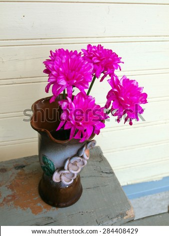 Three purple flowers in ceramic vase on wooden bench        - stock photo