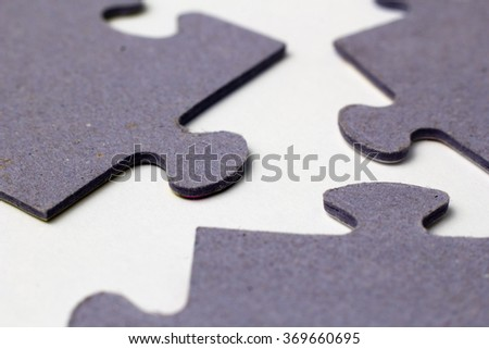 three puzzle pieces close up on paper - stock photo