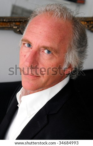 three quarter face portrait of handsome professional blue eyed older man. - stock photo