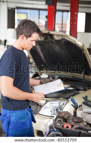 Three-quarter length of mechanic holding a work order - stock photo