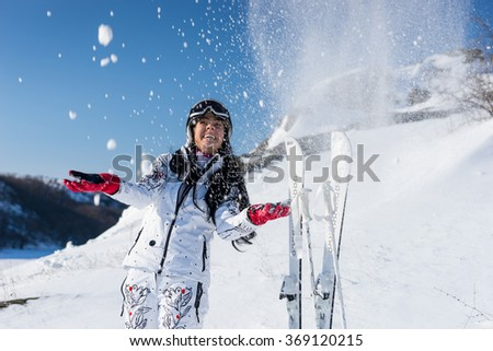 Three Quarter Length of Young Playful Woman with Skis and Poles Tossing Snow in Air on Snow Covered Mountainside on Bright Day with Blue Sky and Warm Sunshine - stock photo