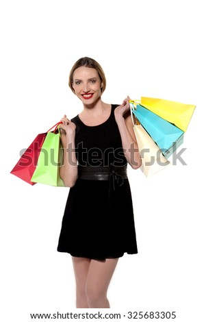 Three quarter length portrait of a young woman holding colored shopping bags. Studio shot isolated on white. - stock photo
