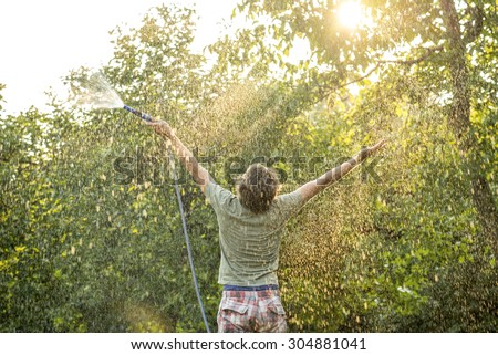 Three-Quarter Rear View Shot of a Man Holding a Garden Hose and Raising his Arms for Happiness While Facing at the Green Trees During Sunrise. - stock photo