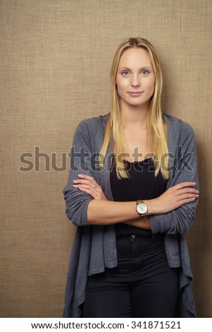 Three Quarter Shot of a Confident Young Businesswoman Looking at the Camera with Arms Crossing Over her Chest Against Brown Wall. - stock photo