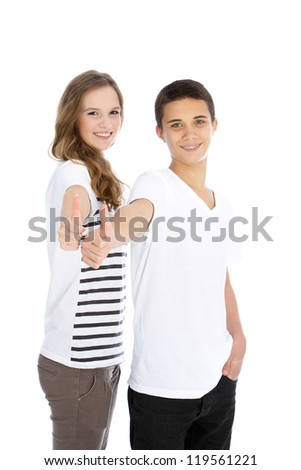 Three quarter studio portrait of an attractive young teenage brother and sister giving a thumbs up gesture isolated on white - stock photo