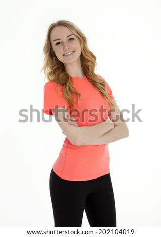 Three quarter view of pretty teenage girl, arms crossed, standing on white background. - stock photo