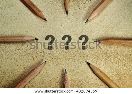 Three question marks surrounded with pencils on grunge background - stock photo