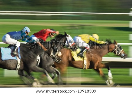 Three racing horses neck to neck in fierce competition for the finish line - stock photo