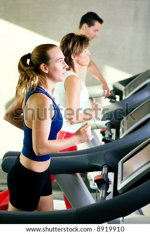 Three rather dynamic people on the treadmill running