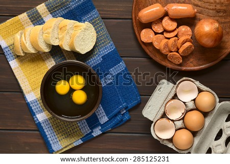 Three raw eggs in rustic bowl with baguette slices, sausage, onion and egg box with eggs and eggshells, photographed overhead on dark wood with natural light - stock photo