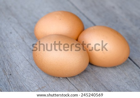 Three raw eggs on a wood table - stock photo