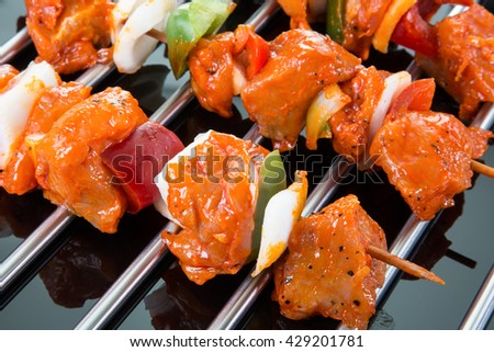 Three raw shaslik skewers on a cooking grate with reflections on the black ground.