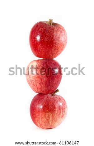 Three red and yellow gala apples balanced tall on each other on a white isolated background. - stock photo