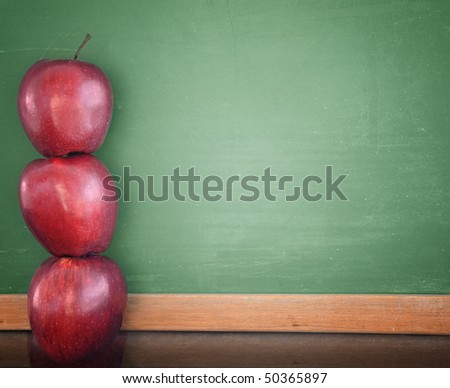 Three red apples are stacked up and leaning against a green school chalkboard. Use the photo for a classroom, school or education concept. - stock photo