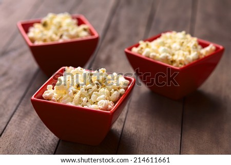 Three red bowls of freshly prepared salted popcorn (Selective Focus, Focus one third into the popcorn in the first bowl) - stock photo