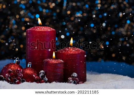 Three Red Candles in snow with snowfall - stock photo