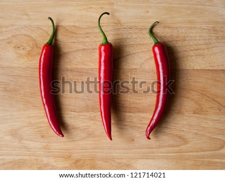 Three red chillis on wooden background - stock photo