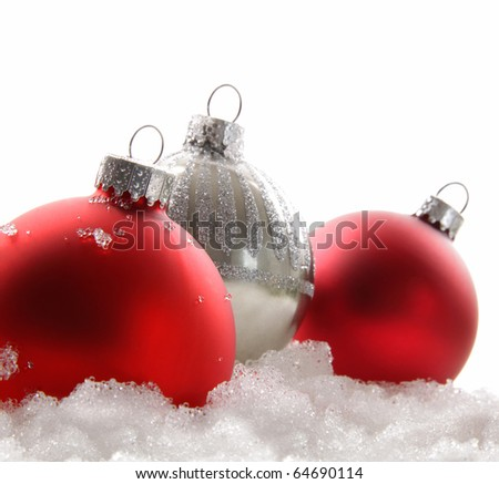 Three red christmas balls in the snow on white