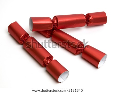 Three red Christmas English party crackers isolated over white.