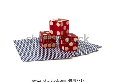 three red dice on five upside down playing cards with blue pattern, shot in studio on white background