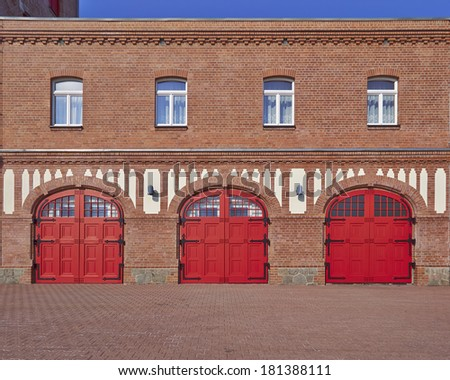 three red doors and four windows, fire squad station, in Saxony, Germany  - stock photo