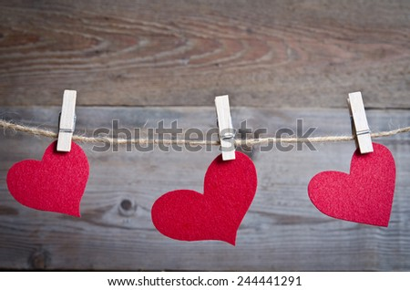 Three Red fabric hearts hanging on the clothesline on three clothespins . On old wood background. - stock photo