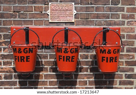 three red fire buckets on hooks ready for an emergency