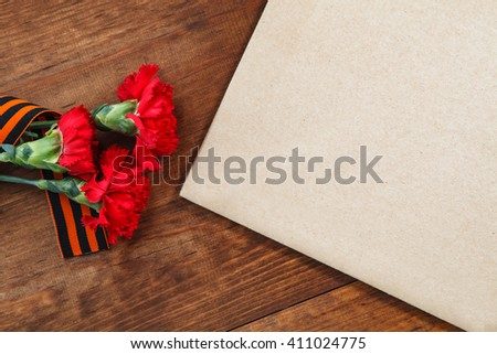 three red flower and paper on a wooden background. selective focus image - stock photo